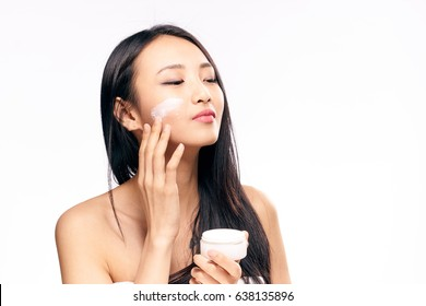 Korean woman puts cream on face