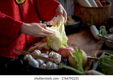 Korean woman is wearing a traditional hanbok, she making Kimchi which is a fermentation food preservation of Korean people consisting of many fresh vegetables and fruits