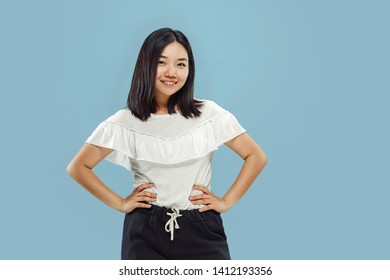 Korean young woman's half-length portrait on blue studio background. Female model in white shirt. Standing and smiling. Concept of human emotions, facial expression. Front view.