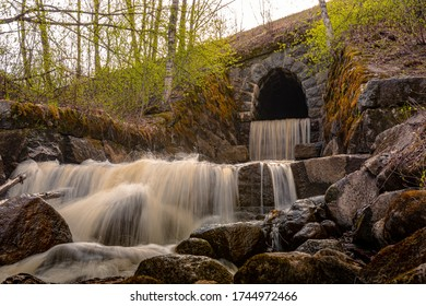 Korkeakoski waterfall created by a small river flowing through an old stone tunnel built under the railway. Spring evening with leaves just starting to open up. Long exposure photo of flowing water.