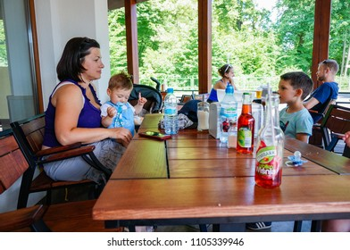 Kornik, Poland - May 26, 2018: Woman with baby and boy sitting by a wooden table of a restaurant