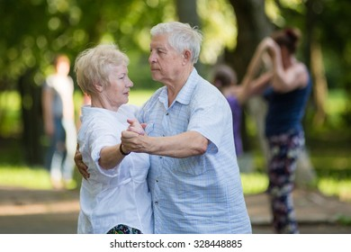 KOROLEV, MOSCOW REGION, RUSSIA - SUMMER, 2015: Smiling couple of old men and woman are dancing at open-air event at the city of Korolev, Moscow region, Russia, Summer, 2015
