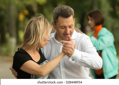KOROLEV, MOSCOW REGION, RUSSIA - SUMMER, 2015: Smiling couple of men and woman are dancing Argentinean tango at open-air event at the city of Korolev, Moscow region, Russia, Summer, 2015