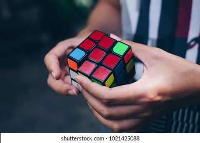 Koronadal City, PH – October 31, 2017: Rubik's Cube was invented in 1974 by Hungarian sculptor and professor of architecture Erno Rubik. Young lady's hands trying to solve the puzzle.