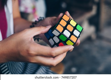 Koronadal City, PH – October 31, 2017: Rubik's Cube was invented in 1974 by Hungarian sculptor and professor of architecture Erno Rubik. Young lady trying to solve the puzzle. Side view. Close-up.