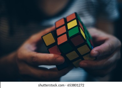 KORONADAL CITY, PHILIPPINES – JANUARY 28, 2017: Rubik's Cube was invented in 1974 by Hungarian sculptor and professor of architecture Erno Rubik. Hands of a young lady trying to solve the puzzle.
