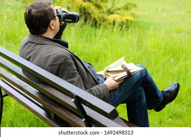 KOROSTEN - AUG, 28, 2018: A man in black clothes sits on a bench drinking water and reading a book