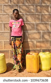 Korr, Marsabit / Kenya - October 2017. Young Kenyan girl is standing next to yellow jerry cans full of water in drought-prone area of Korr, Kenya. World water day.