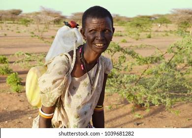 Korr, Marsabit / Kenya - October 2017. Elderly woman is carrying heavy containers full of water in drought-prone area of Korr, Kenya. World water day.