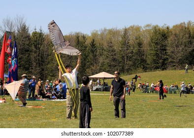 KORTRIGHT CENTER  MAY 06: Man with kite of bird shape at  Four Winds Spring Kite Festival in May 06 2012 in Kortright Center in Ontario, Canada.