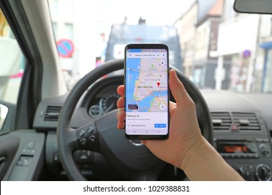 KORTRIJK, BELGIUM - JANUARY 28TH 2018: a hand holding a brand new Samsung Galaxy S8 phone with the Google Maps app with New York city on the touch screen, inside a Mercedes car. Illustrative editorial