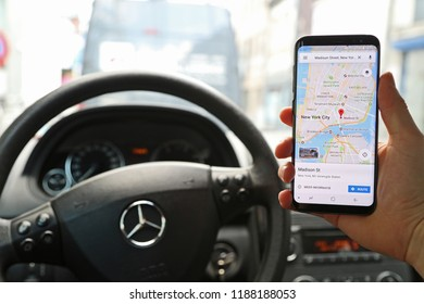 KORTRIJK, BELGIUM - JANUARY 28TH 2018: a hand holding a brand new Samsung Galaxy S9 phone with the Google Maps app with New York city on the touch screen, inside a Mercedes car. Illustrative editorial