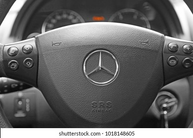 KORTRIJK, BELGIUM -JANUARY 30ST 2018: The famous logo on the steering wheel of a Mercedes Benz with a black interior. The keys are in the ignition. The gauges in the background. Illustrative editorial