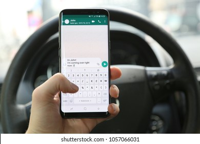 KORTRIJK, BELGIUM -JANUARY 30ST 2018: Person texting and driving on a Samsung Galaxy S8 phone. The left hand typed a message on the WhatsApp app. Concept of dangerous behavior. Illustrative editorial.