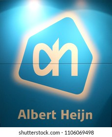 KORTRIJK, BELGIUM- MAI 16TH 2018: The logo and name of the popular Dutch supermarket Albert Heijn, also known as the AH. The bright blue sign is lit up by two overhead lights. Illustrative editorial.