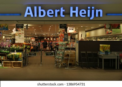 KORTRIJK, BELGIUM- MAY 2ND 2019: The logo and name of the popular Dutch supermarket Albert Heijn, also known as the AH. The bright blue sign is showing the entrance of the shop. Illustrative editorial