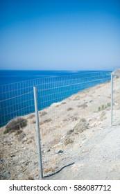 Kos (Cos) island in Greece. Fence, beautiful blue sea and sky on the beach.