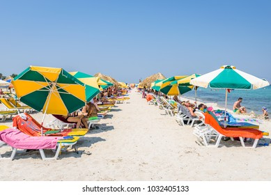 Kos, Greece/ Dodecanese - August 08 2017: Beautiful sunny coast view to the greek mediterranean blue sea with crystal clear water and pure sandy beach while some tourists are sunbathing and relaxing