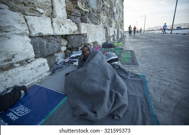 KOS, GREECE - FEB 28, 2015: Unidentified war refugee sleeping on the street. More than half are migrants from Syria, but there are refugees from other countries - Afghanistan, Pakistan, Iran, Mali.