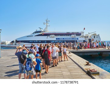 Kos, Greece - July 4, 2018. A herd of tourists boarding in a ferry at the harbour of Kos, a Greek island of the South Aegean region, Greece.