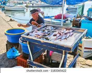Kos, Greece - July 4, 2018. A Greek fisherman baiting hooks and selling fresh fish at Kos fishing port, a Greek island of the South Aegean region, Greece.