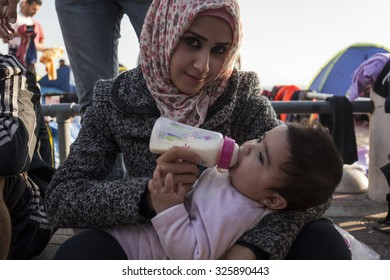 Kos, Greece - October 10, 2015: Syrian refugee is feeding her child at a volunteer's camp
