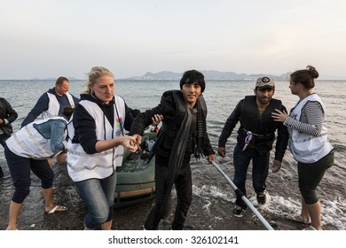 Kos, Greece - October 11, 2015:  Volunteers from Holland are helping a man from Pakistan who came on dinghy boat from Turkey to Kos island, Greece