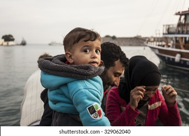Kos, Greece - October 17, 2015:Migrant is carrying a child in the port of Kos town on the Kos island, Greece.