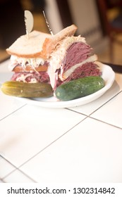Kosher deli combination sandwich pastrami corned beef tongue cole slaw and Russian dressing on seeded Jewish rye bread with garlic and sour pickles New York restaurant delicatessen