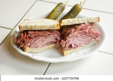 Kosher New York City deli corned beef tongue combination sandwich on rye bread with pickles