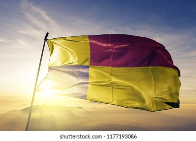 Kosice region of Slovakia flag textile cloth fabric waving on the top sunrise mist fog