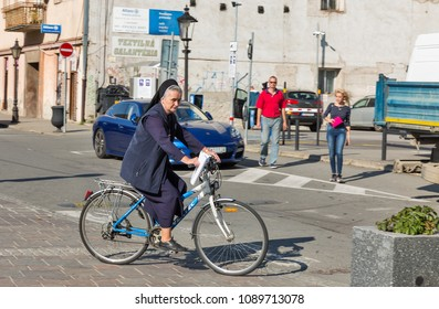 KOSICE, SLOVAKIA - OCTOBER 02, 2017: Senior nun rides bicycle along street in Old Town. It is the largest city in eastern Slovakia in 2013 was the European Capital of Culture.