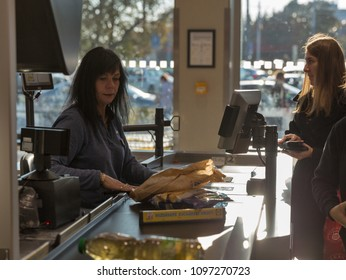 KOSICE, SLOVAKIA - OCTOBER 02, 2017: Woman cashier works in a Lidl supermarket. Lidl is a German global discount supermarket chain, that operates over 10,000 stores across Europe and the United States