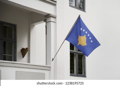Kosovo flag hanging on a pole in front of the house. National flag waving on a home displaying on a pole on a front door of a building and raised at a full staff.