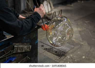 KOSTA, SWEDEN - MARCH 12 2020: man turns a blow pipe with which a glass object is made and forms a neck to the glass object with pliers in glassworks Kosta in Sweden