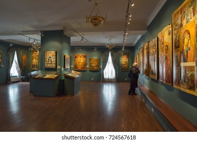 KOSTROMA, RUSSIA - MAY 06, 2017: Collection of ancient Russian orthodox icons in the Ipatiev Monastery. Woman looks at the icons at an exhibition