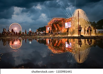 KOSTRZYN NAD ODRA, POLAND - AUGUST 3, 2017: Festival Przystanek Woodstock - fans bath in the mud in front of the stage with reflection on the water.