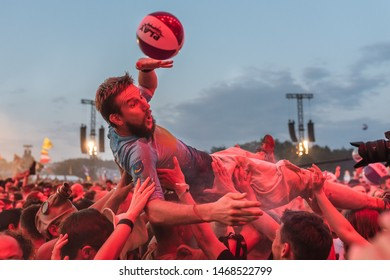 KOSTRZYN NAD ODRA, POLAND - AUGUST 1, 2019:  25th Pol'and'Rock festival - the audience carry the man under the stage and a ball in the background.