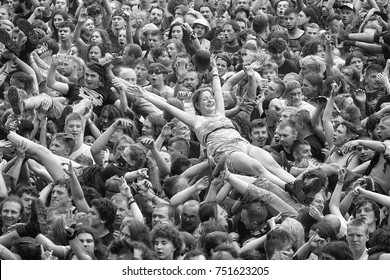Kostrzyn, Poland - August 05, 2017: A woman crowd surfing at a concert during the 23rd Woodstock Festival Poland. Festival is among the biggest open air festivals in the world.