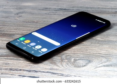 Koszalin, Poland – 04 May, 2017: Black Samsung Galaxy S8 on wooden table. Samsung S8 are new generation smartphone from Samsung. The Samsung S8 is smart phone with multi touch screen