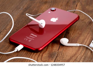 Koszalin, Poland – December 04, 2018: Red iPhone XR on a wooden table with white earphones. The iPhone XR is smart phone with multi touch screen produced by Apple Computer, Inc.