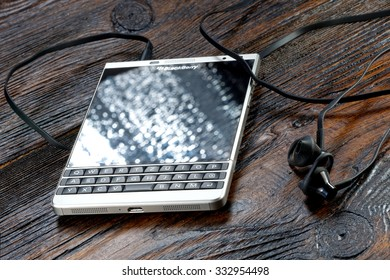Koszalin, Poland â??  October 29, 2015: Blackberry Passport Silver Edition on wooden table. Devices displaying the applications on the home screen. The BlackBerry phone is smart phone with touch screen.