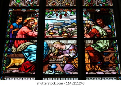 KOSZEG, HUNGARY - AUGUST 10, 2012: Stained glass of Sacred Heart Church in Koszeg, Hungary. Gospel depiction of the Anointing of Jesus where a sinful woman washes Jesus' feet with her tears.