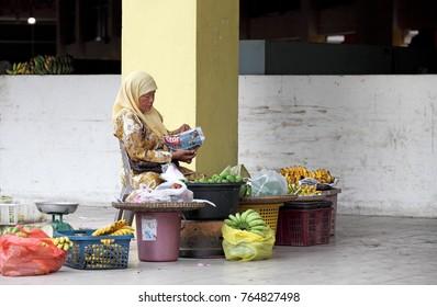 KOTA BAHRU, MALAYSIA - MAR 6, 2011: A lady peddler at the walkway in Siti Khadijah Market in Kota Bahru, Kelantan, Malaysia. Siti Khadijah Market is an all lady mkt in the Muslim enclave of Kelantan.