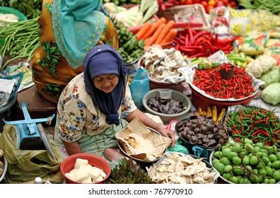 KOTA BAHRU, MALAYSIA - MAR 6, 2011: An old lady vendor at her stall in Siti Khadijah Market in Kota Bahru, Malaysia. Siti Khadijah Market is an all lady market in the muslim enclave of Kelantan.