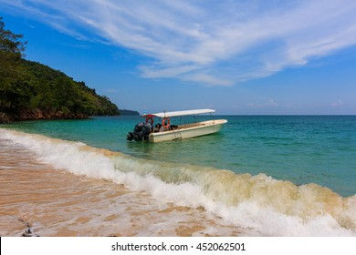Kota Belud, Sabah, Malaysia - July 09, 2016 : A scuba diving boat is anchored in a beautiful tropical bay of turquoise water and a bright, blue vibrant sky with patchy clouds.