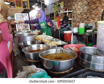 Kota Bharu, Kelantan. April 28, 2018. A woman performing transaction in Kelantan, an east cost country in Malaysia is business as usual despite being ruled by Islamist opposition party for 20 years