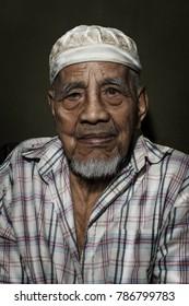 Kota Bharu, Malaysia - January 03, 2018 : An old man wearing a hat sitting in close up shot in home mini studia in Kelantan