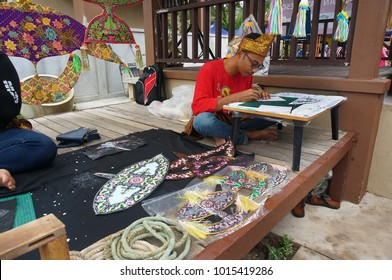 Kota Bharu, Malaysia - January 27, 2018 : A male Wau Bulan (local kite) maker are drawing a flourish shape to make a kite under the wooden hut in Kelantan.
