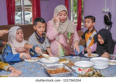 Kota Bharu, Malaysia -June 17th, 2018 : The family ate the food while visiting their relatives during Eid al-Fitr celebration .Family, Happiness and Forgiveness Concept.
